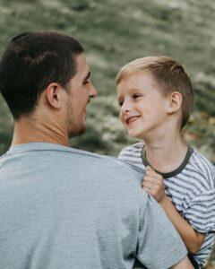 Asperger - Niño sonríe en brazos del padre