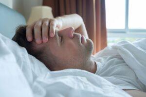 Migraña emocional - hombre en la cama con dolor