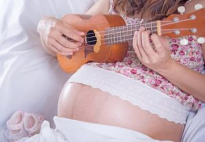 Música durante el embarazo - Mujer embarazada tocando ukelele